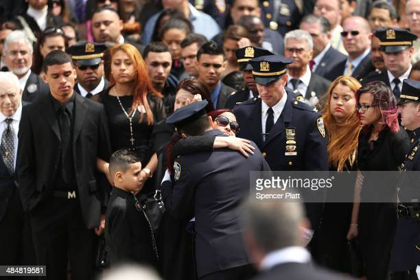 Fallen New York Police Department officer Dennis Guerra's wife Cathy hugs an officer outside of Rose of Lima Church in Far Rockaway Queens during the...
