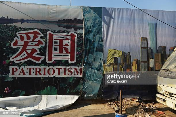 A fallen poster reveals a previous poster about patriotism underneath on the side of a construction site in Beijing on February 10 2015 China's...