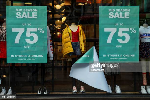 A fallen sale sign hangs between two others at an Urban Outfitters store on Oxford Street in London UK on Thursday March 30 2017 UK retailers enjoyed...
