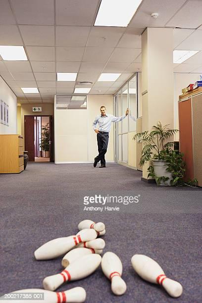 Fallen skittles on office floor, man in background smiling