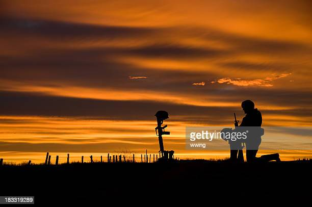 fallen soldier - soldier praying stock photos and pictures