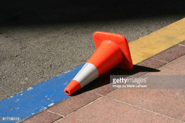 fallen traffic cone on street - cone shape stock photos and pictures
