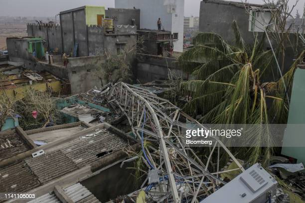 A fallen transmission tower lies on the roof of damaged houses after Cyclone Fani passes in the Puri district of Odisha India on Saturday May 4 2019...