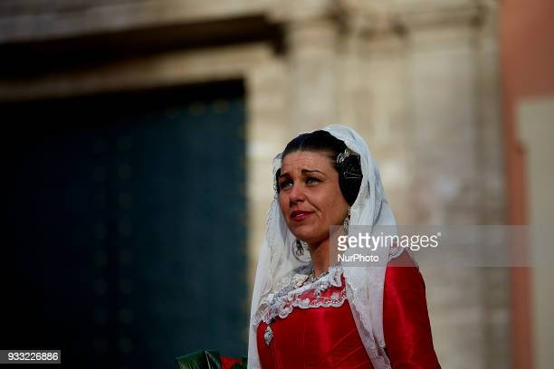 A fallera dressed up in traditional costume prepares to present flowers to Saint Mary during Las Fallas Festival on March 17 2018 in Valencia Spain...