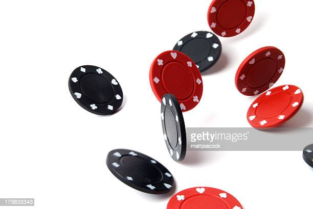 Falling black and red gambling chips on white surface