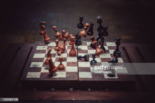 falling chess pieces on the chessboard - chess stock pictures, royalty-free photos & images
