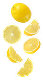 falling, hanging, flying whole and half piece of lemon fruits isolated on white background with clipping path