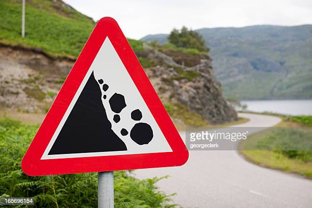 falling rocks warning road sign - warning sign stock pictures, royalty-free photos & images