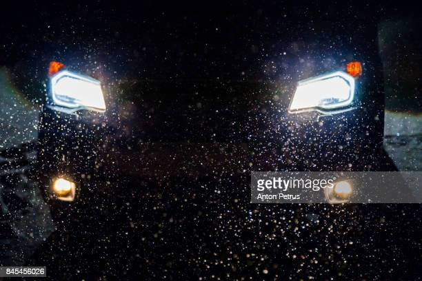Falling snow in the headlights of the car at night