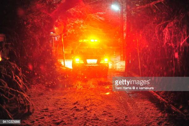 Falling snow lighted up by police car red light on snow-covered road at the night