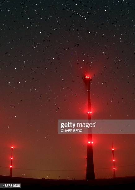 A falling star crosses the night sky behind illuminated windmills near Gemuend western Germany during the peak in activity of the annual Perseids...