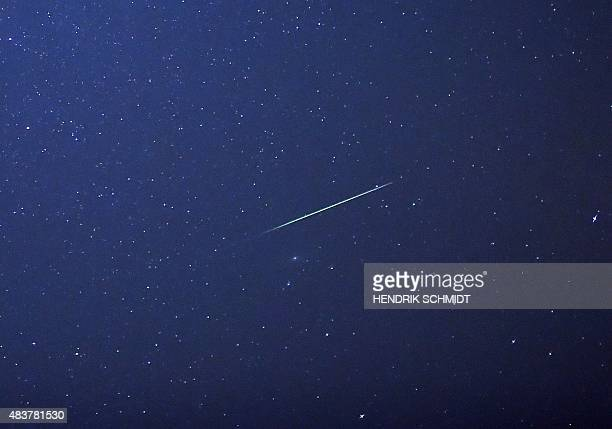 A falling star crosses the night sky over Halle / Saale eastern Germany during the peak in activity of the annual Perseids meteor shower on August 13...