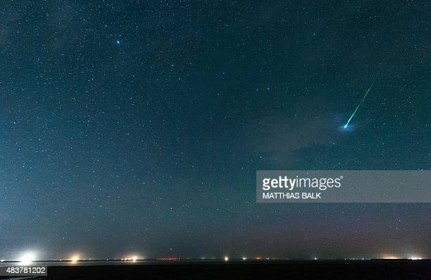 A falling star crosses the night sky over the North Sea coast in Pilsum northwestern Germany during the peak in activity of the annual Perseids...