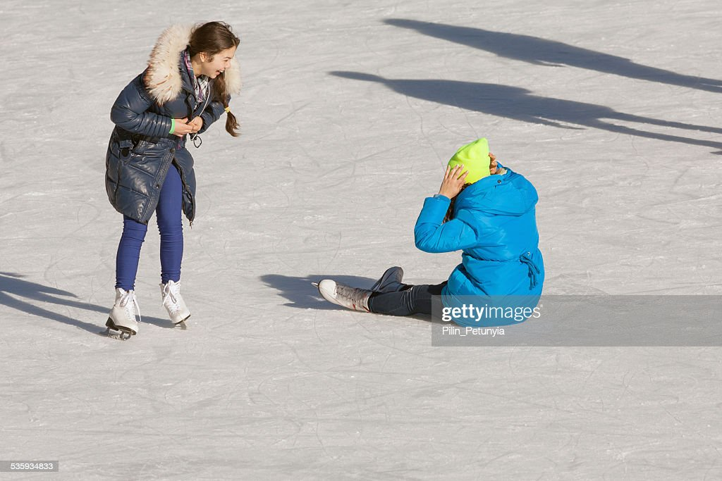 falling teenager on the ice rink : Stock Photo