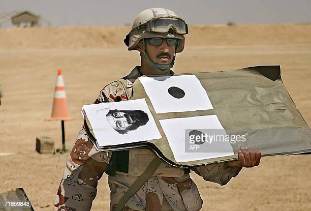 A picture released by the US marines 04 July 2006 shows Iraqi Cpl Ahmed Waleed Muhid bringing a target sheet showing he face of alQaeda leader Osama...