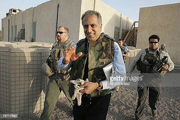 US Ambassador to Iraq Zalmay Khalilzad wearing a flack jacket and surrounded by bodyguards waves as he leaves the Civil and Military Operation Center...