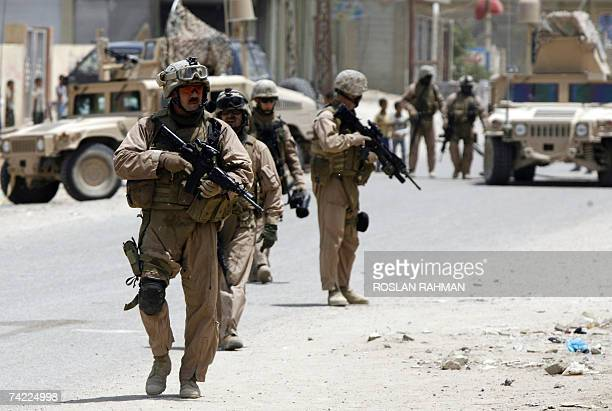 Marines keep watch as the military's civil affairs personnel visit schools in the restive southern city of Fallujah, 50 kms west of Baghdad 23 May...