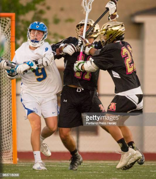 Falmouth attack Tom Fitzgerald passes the ball opposed by Thornton Academys Cameron Houde and Anthony Bracamonte during varsity lacrosse action in...