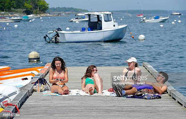 Falmouth friends enjoy working on their tans during the hot sunny day on the dinghy floating dock at Falmouth Town Landing Just back from college are...