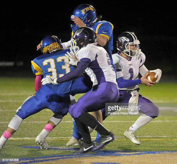Falmouth vs Marshwood football game Marshwood quarterback Cole McDaniel slips away from a pair of Falmouth defenders including Riley Reed