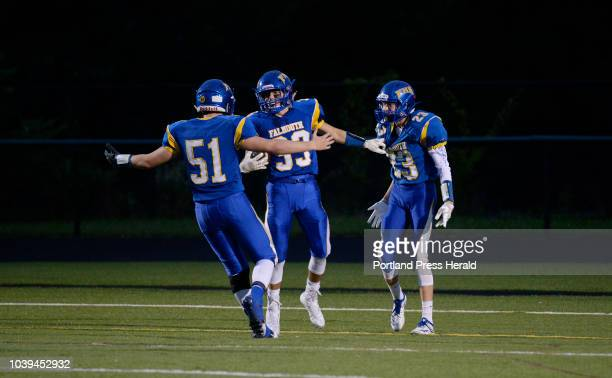 Falmouth's Riley Reed center is congratulated by teammates after scoring a first half touchdown Friday September 21 2018 L to R are CJ Jones Reed and...