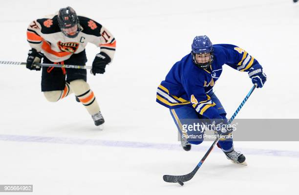 Falmouth's Tyler Baker takes the puck up the ice as Biddeford's Curtis Petit moves in on defense Wednesday January 10 2018