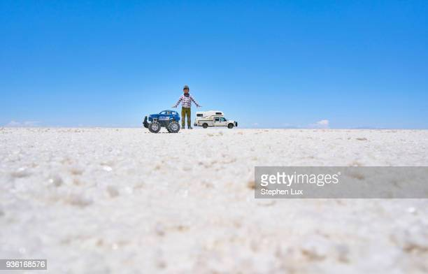 false perspective image of boy and toy truck on salt flats, standing taller than recreational vehicle in background, salar de uyuni, uyuni, oruro, bolivia, south america - ウユニ ストックフォトと画像
