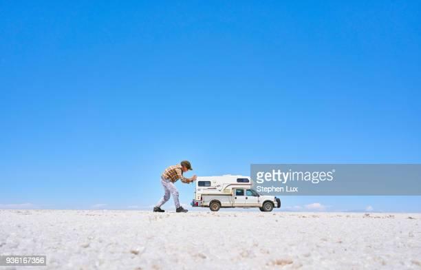 false perspective image of boy on salt flats, pretending to push recreational vehicle, vehicle in background, salar de uyuni, uyuni, oruro, bolivia, south america - ウユニ ストックフォトと画像