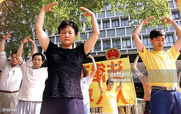 Falun Gong adherents practice breathing and meditation exercises during a protest outside the Central Government Offices 29 October 1999 in Hong Kong...