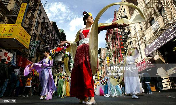 Falun Gong followers dance as they parade through Chinatown April 10 2004 in New York City Thousands marched in and attended the parade which was...