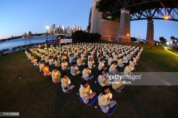 Falun Gong Practitioners hold candles for a vigil to mark the 14th anniversary of the beginning of the persecution of Falun Gong in China on July 21...