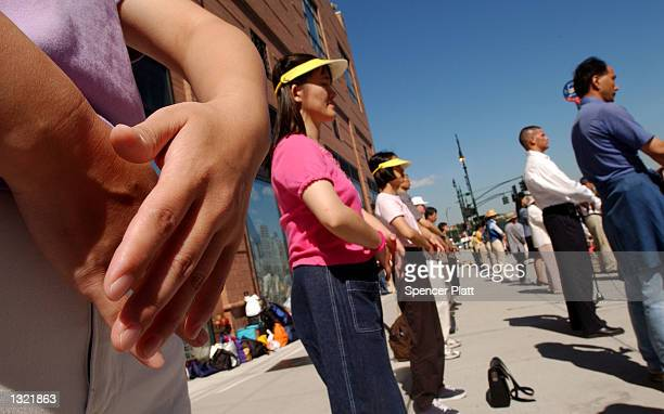 Falun Gong practitioners meditate in front of the Chinese consulate July 3, 2001 in New York City. Hundreds of Falun Gong followers are walking to...