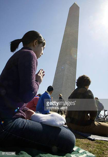 Falun Gong practitioners meditate in the shadow of the Washington Monument 28 March 2002 in Washington DC The practitioners are on a sixday round the...