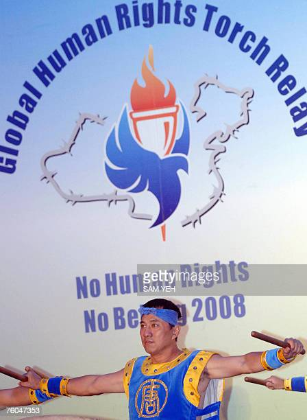 A falungong member performs in front of a Olympic logo during a demonstration in Taipei 10 August 2007 Taiwan's human rights activists rallied to...