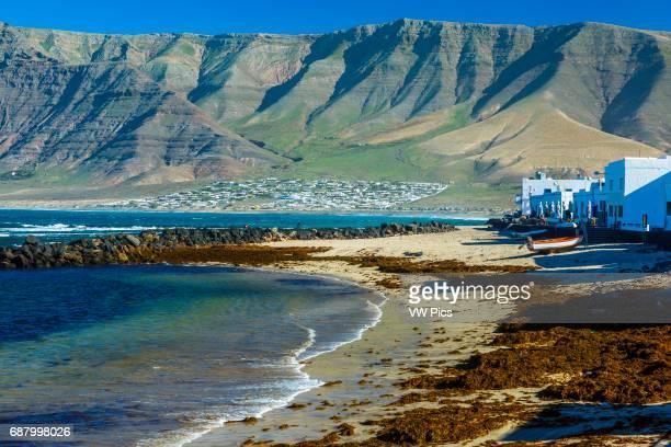 Famara Beach, houses and mountain range. Caleta de Famara, Lanzarote, Las Palmas, Canary islands, Spain, Europe.