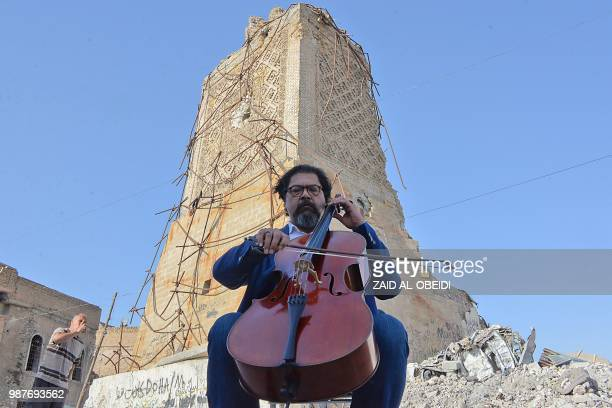 Famed Iraqi maestro and cello player Karim Wasfi performs in front of the AlHadba minaret at the the Great Mosque of alNuri in Mosuls warravaged Old...