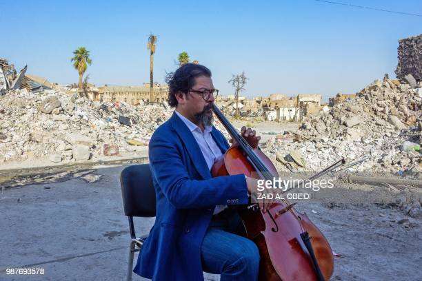 Famed Iraqi maestro and cello player Karim Wasfi performs in front of the Great Mosque of alNuri in Mosuls warravaged Old City on June 29 one year...