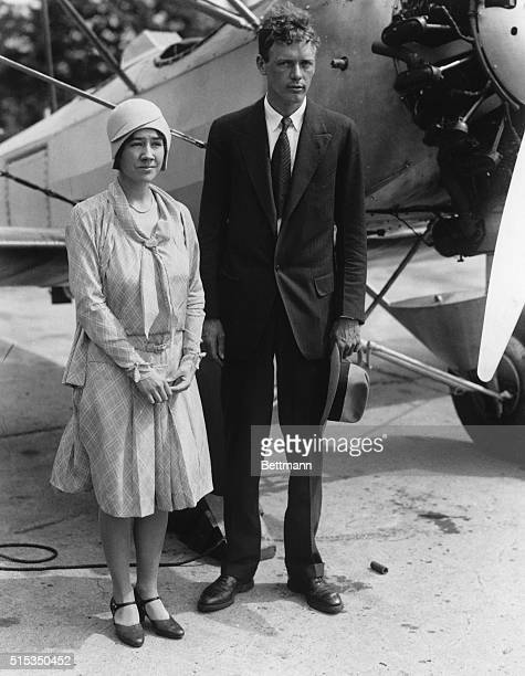 Famed pilot Charles Lindbergh and his wife Anne Morrow Lindbergh pose in front of a biplane shortly after their marriage