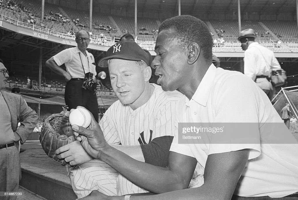Famed pitcher Satchel Paige (right) shares pointers with New York Yankee pitcher Whitey Ford prior to the start of a New York-Chicago game in Yankee Stadium. Paige leads a group of Negro League All-Stars playing in the stadium for an exhibition game. New York, August 17, 1961.