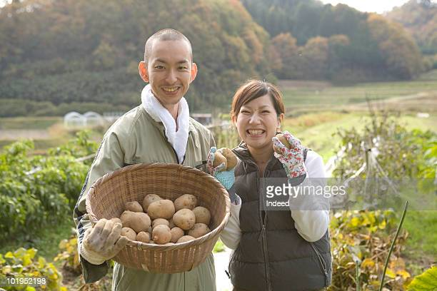 Famer couple holding potatoes, smiling, portrait