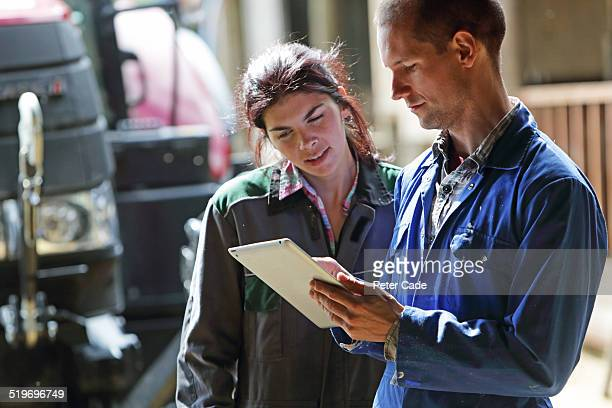 Famers couple looking at tablet . farm and tractor