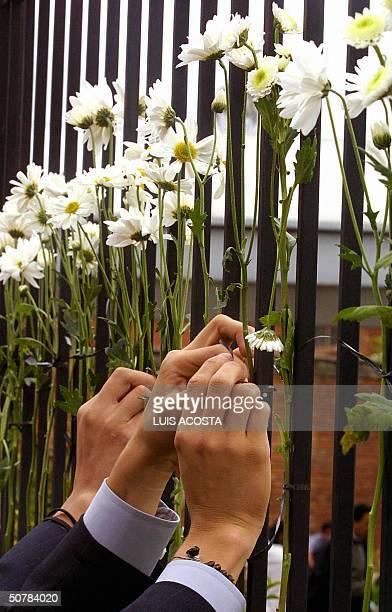 Familiares y amigos colocan ofrendas florales frente al colegio Agustiniano en Bogota el 29 de abril de 2004 Un total de 22 ninos y un adulto muertos...