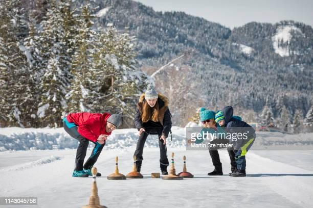 familie beim eisstock schießen am weissensee - winter tourismus - tourismus stock pictures, royalty-free photos & images