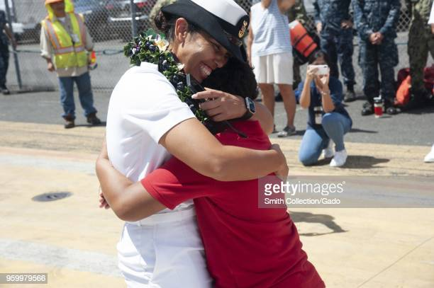 Families and friends hugging and celebrating the arrival of the Arleigh Burkeclass guidedmissile destroyer USS Halsey at Joint Base Pearl...