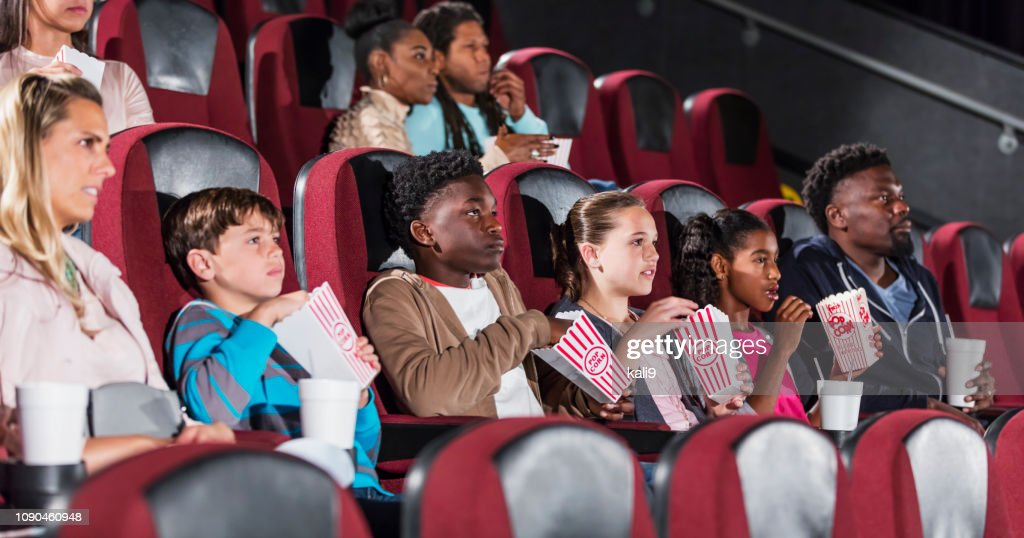 families and friends in movie theater, eating popcorn : Stock Photo