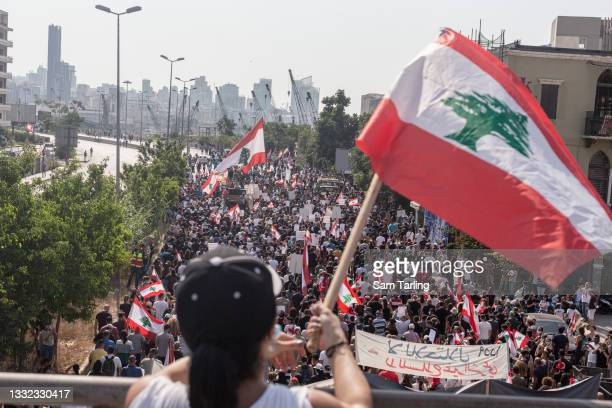 Families and friends of the ten firefighters who died during the Beirut port explosion march toward the port before an anniversary commemoration, on...