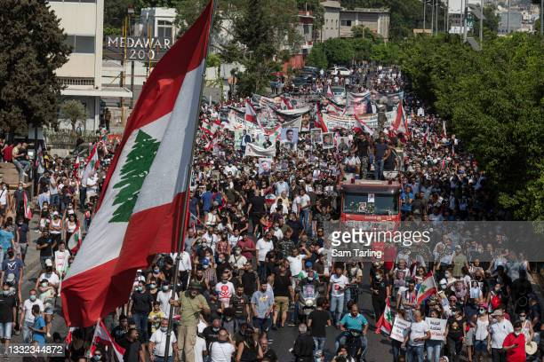 Families and friends of the ten firefighters who died during the Beirut port explosion march toward the port before an anniversary commemoration on...