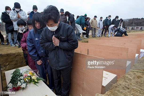 Families and relatives of the dead cry as they identify their family members at a temporary burial ground on March 25 2011 in Higashimatsushima...