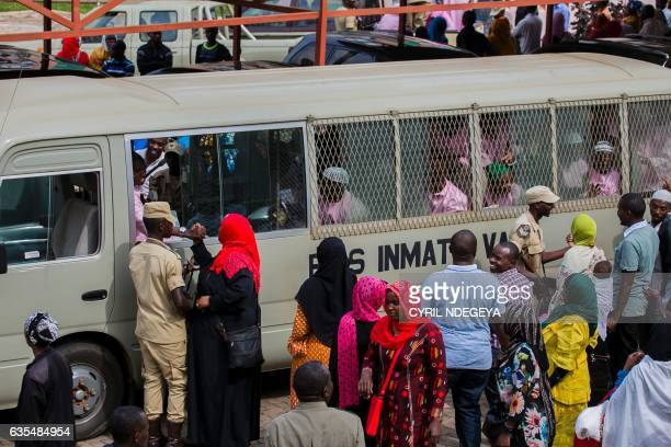 Families and relatives of the suspects gather around the bus that carries the accused men outside the High Court of Rwanda in Kigali on February 15...