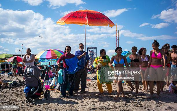 Families and teenagers congregate on the sand July 24 2015 at Coney Island Beach in the Brooklyn borough of New York